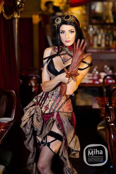Crimson Steampunk Burlesque (brown and tan brocade underbust corset with matching high low hem skirt, tan brown leather gloves, goggles, necklace and pocket watch, black bra, black garters with thigh high fishnet stockings, collar) - For costume tutorials, clothing guide, fashion inspiration photo gallery, calendar of Steampunk events, & more, visit SteampunkFashionGuide.com