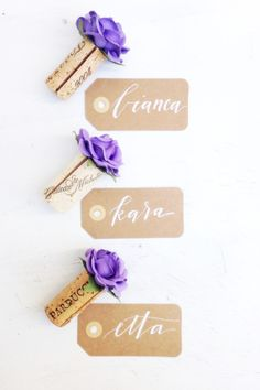 Purple wedding wine cork Place Card Holders by KVW & kraft name tag calligraphy by Charlie Whiskey lettering + design. Explore more unique wedding place card holder ideas at www.karasvineyardweddingshop.com