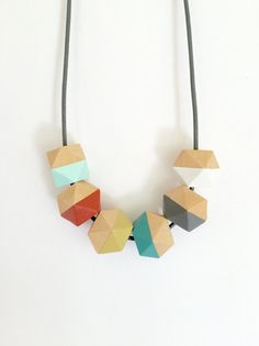 This modern geometric wooden bead necklace consists of six 16mm faceted beads, hand painted in a chic color block style, and strung on a DARK GREY
