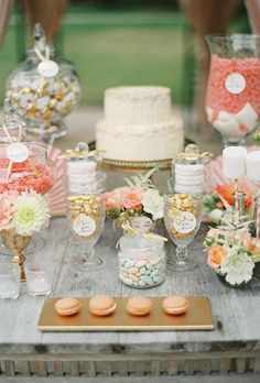 A pretty pastel-themed dessert bar with peach macarons, golden chocolate eggs, and pink jelly beans. Yum!