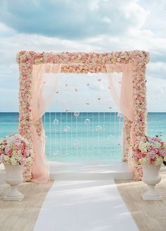 Overlooking the turquoise Bahamian waters, a pink and white arbor covered in flowers drips with crystal strands and glass bubbles filled with flower petals. Click to view the Top 10 Most Beautiful Ceremony Arbors.