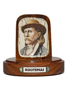 """Kootenai"" Color scrimshaw on ancient mammoth ivory by Gary Williams. Really like the way the scrimshander has used the natural color in the outer bark of the mammoth ivory to compliment the tones and shades in the portrait, especially in the hat. Portrait of a famous Canadian pioneer. Size: 4 1/4""L x 2 1/2""D x 41/4""H  Price: $1650.00  -- on ScrimshawGallery.com #scrimshaw"
