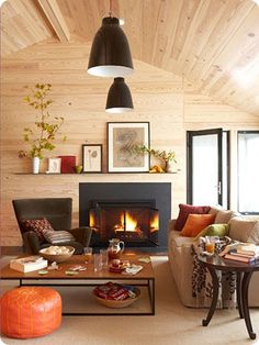 Love the dash of pumpkin orange on the pouf. Plus the black trim with the pine paneling.