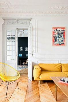 Jaune ocre sur le canapé, jaune vif pour le fauteuil, le tout sur un sol en bois blond et des murs blancs aux moulures classiques. Un beau mélange !
