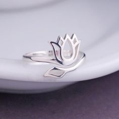 This lotus flower ring is sterling silver and fits most! Adjusts from approximately a size 6 to a size 9. Ready to ship and perfectly pairs with all of our personalized jewelry.