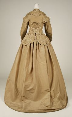 American Silk Dress, 1865-69. Pre-Victorian fashion often seemed to make use of odd accents, ruffles, pleats, and bows on otherwise plainly-shaped dresses, as seen on the back and shoulders of this one.