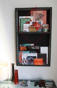 Libreria bacheca progettata per riporre libri e decorare pareti. Strutture in legno e schiena in tessuto.