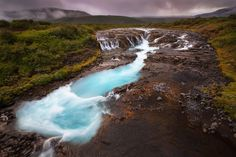River Blues - Bruarfoss Iceland  This small waterfall is a little off the beaten path but is particularly striking for its geothermal blues and the steam it creates in the cold air. There is a bridge over the river from which this image was taken.  Photographer : Marianne Lim