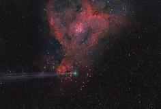 A comet streaks in front of glowing red celestial gas cloud.