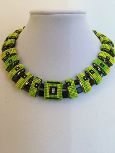 """""""Hip to Be Square"""", 2018. I remain inspired by the use of two-hole carrier beads and decided to design a geometric necklace built upon layers of squares and cubes. In order to achieve the crisp shapes I wanted, I utilized square stitch vs. peyote stitch to cover the carrier beads."""