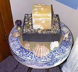 Sacred Space: Stone carved water fountain surrounded by a collection of sea shells and a healing amethyst sphere