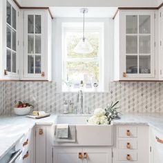 Gorgeous u-shaped white kitchen features a a window lit by a glass pendant hung above a farmhouse sink fixed to white shaker cabinets accented with leather pulls and a honed white marble countertop.