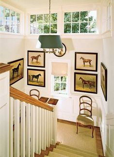 Nineteenth-century equine paintings from the stables of a castle in Germany hang in the formal stair hall, which connects the entrance gallery with the library on the top floor. The 18th-century walnut chairs are French.