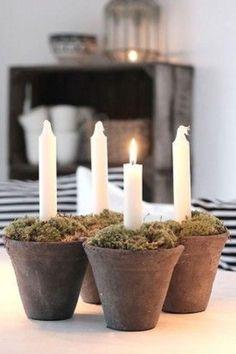 Centro de mesa compuesto por, pequeñas macetas de barro con musgo y velas blancas.