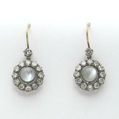 Antique Victorian moonstone earrings are encircled by a cluster of old European cut diamonds. The clusters have a total carat weight of 1.82cts, set in silver with 14k gold shepherds hooks.