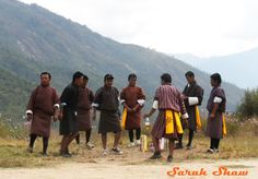 Bhutanese Men in Gho, robes that are part of the national dress, at an archery competition. via WanderShopper