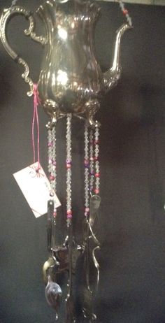 Silver plated teapot repurposed into a beautiful & functional wind chime. Clear beads along with purplish-ping glass beads help suspend the curled cutlery