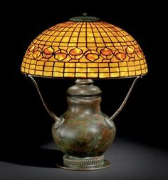 A 'Leaf and Vine' Dichroic Leaded Glass and Bronze Table Lamp, circa 1910  18½ in. (47 cm.) high, 16 in. (40.7 cm.) diameter of shade