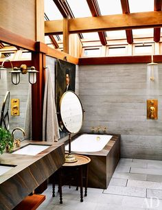An antique brass mirror tops a vintage Moroccan tea table in the master bath, whose tub, sinks, sconces, and fittings are by Waterworks.