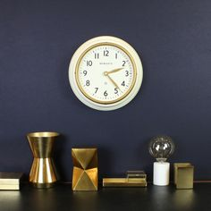 The Cookhouse wall clock in Linen White by Newgate Clocks. A cream metal wall clock with vintage brass bezel. Dark blue wall interior. Brass homeware and desk accessories.