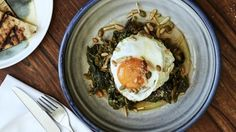 Wild greens braised in tomato, olive oil, grain, nuts and fried eggs