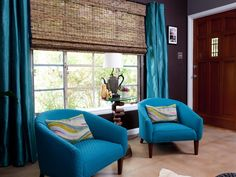 Two vintage club chairs are upholstered in a bright blue fabric to break up the dark, moody colors in this living room designed by HGTV's Property Brothers. The blue curtains and rattan window treatment add texture.