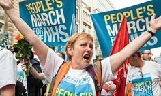 A woman wearing a 'People's March For The NHS' shirt holds her arms up while chanting. Photograph: Mel Pressmen/Demotix/Corbis