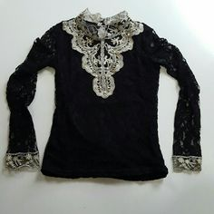 """Classic Lace Blouse This lovely top is black lace with a silky second layer underneath the front and back but not the long sleeves which are capped with gold lace floral lace. The neck line is a high lqrge collar that does not fold over but is more like a turtle neck. The front has some gold and white pearl plastic beads sewn on to the golden and cream colored lace V front. This is brand new and unused, best fits a size small. The chest measures 31""""  waist 27"""" and it is 21"""" long. Tops…"""