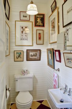 Tiny, classic powder room; charming 1913 Craftsman in Portland. Ladds addition powder room with gallery wall. Alice Design and Domestic Arts. Built by Hammer and Hand in Portland