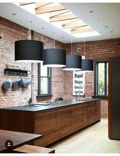 Cuisine bois sombre et briques au mur.