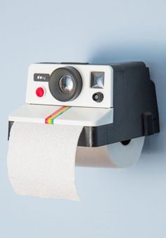 Polaroid camera casing repurposed as a toilet paper dispenser