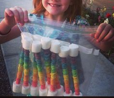 Rainbow snack: marshmallows and fruit loops on a wooden skewer.
