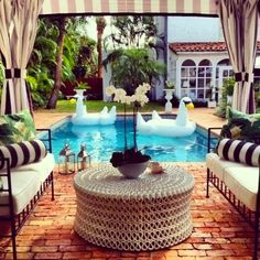 black and white striped patio cover. LOVE the huge swans in the pool, I want one!!