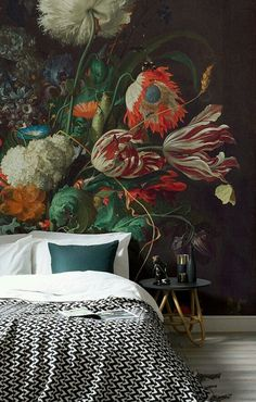 papier peint bleu petrole avec un motif bouquet de fleurs et linge de lit blanc et noir, parquet gris, table de chevet minimaliste