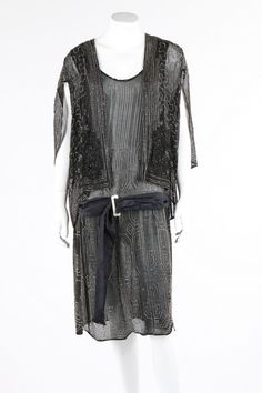 A beaded black crepe flapper dress and similar beaded bolero-capelet, late 1920s. adorned with shimmering silver beads, bust 97cm, 38in.