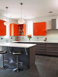 Designer Robin Siegerman chose the upper cabinets' intense hue for its mood-lifting qualities. Studies have shown that the color orange stimulates optimism and a positive outlook. Considering most of us spend a little time each morning in the kitchen, starting each day with a cheery outlook is ideal.