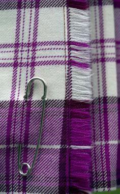 Close up of purple tartan women's skirt and kilt pin.