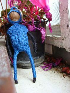 figura de hilo con forma humana, traje azul con capucha