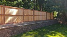 AJB Services replaced a chain link fence with a retaining wall and privacy fence to insulate against road noise on this Lacey property. Wooden Retaining Wall, Building A Retaining Wall, Concrete Retaining Walls, Landscaping Retaining Walls, Privacy Landscaping, Landscaping Ideas, Flagstone Pavers, Concrete Fence, Wooden Fence