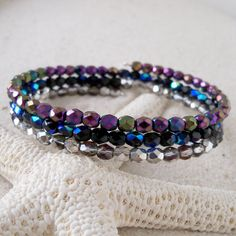 This listing is for an oval, glass beaded memory wire bracelet, with purple, black, and silver/clear AB glass beads. The beads are 4mm Czech