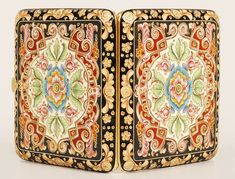 A Russian silver gilt and cloisonné enamel cigarette case, Feodor Ruckert, Moscow, 1896-1908. Both sides lavishly decorated in multi-color shaded enamel scroll, floral, and geometric motifs within a border of stylized amber colored floral designs against a black enamel ground.