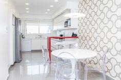 Cocina con barra roja. Empapelado geométrico, porcellanato pulido y muebles de pvc blancos. Mesa tulip y sillas ghost.