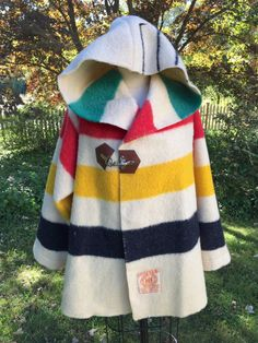 Very collectible vintage Hudson Bay wool blankets have kept people cozy for years. Im using these carefully curated vintage HBC point blankets to make easy-to-wear swing coats with oversized hoods. A leather and nickle clasp secures to keep the wind out, and warmth in! The swing coat is loose and easy to wear with even the bulkiest of sweaters. A selection beautiful blanket colors is available for your consideration . Hudson Bay Point Blankets were introduced in 1780, woven in England of…