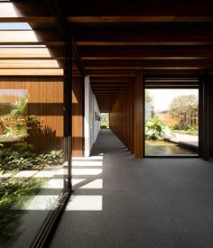 The walkway extends through the glass-walled entrance hall and out the other side to enhance the sense of connection with the garden and landscape beyond.
