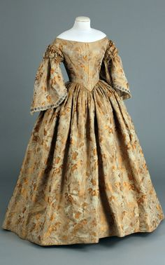 "Ball gown ca. 1855-65. Gold brocaded silk. Chester County (PA) Historical Society: ""The open neckline and the exposed arms of the sleeves indicate that this dress was probably a ball gown. It has a matching capelet, or pelerine that provides a more modest look."" Click through for huge, hi-def image."