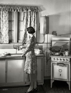 "New Zealand circa 1930s. ""Model at sink in kitchen equipped with Atlas electric stove and Zip water heater."" Studio of Gordon Burt, Wellington."