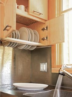 We love the idea of building a dish-drying rack into an upper cabinet. We especially love this design, which provides a seamless stainless steel backsplash and countertop below the cabinet.