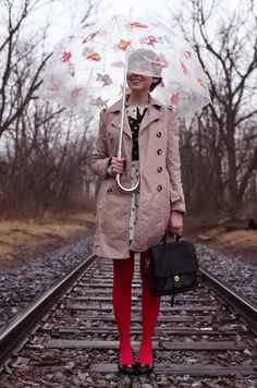 The Clothes Horse. Simple trench coat, black and white print dress and red tights. And of course, a whimsical umbrella.