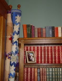 Quilts rolled on wooden closet poles with finials screwed to the ends; tied with ribbons. These are leaning against a bookcase in a corner.  Quilting With Judy Martin -- Lessons, Blocks, and Quilting Products From The World-Reknowned Quilter