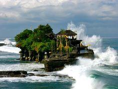 Tanah Lot om de zonsondergang te bekijken. Het heiligdom is gebouwd op een rots, waar bij vloed de zee omheen spoelt. Veel mensen brengen hun offers bij de fraaie zeetempel die bovendien behuisd wordt door de heilige slang.